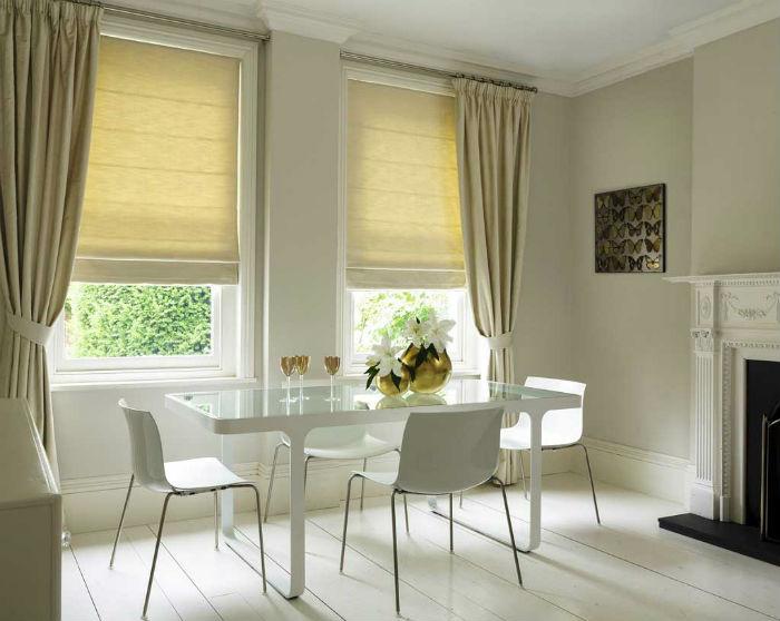 Римские занавесы из плотной ткани надежно защищают от солнца и света фонарей, они прекрасно комбинируются с обычными шторами, один из примеров сочетания показан на фото