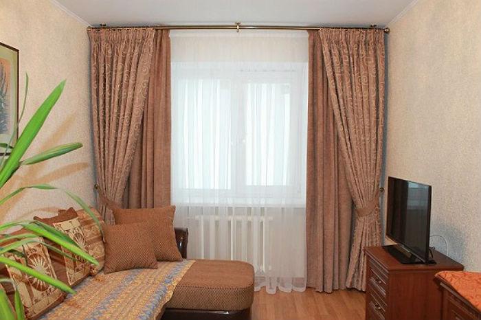 Двойные текстильные занавески в сочетании однотонного полотна и полотна с неброским орнаментом смотрятся очень аккуратно и компактно, такие модели подходят для маленьких комнат
