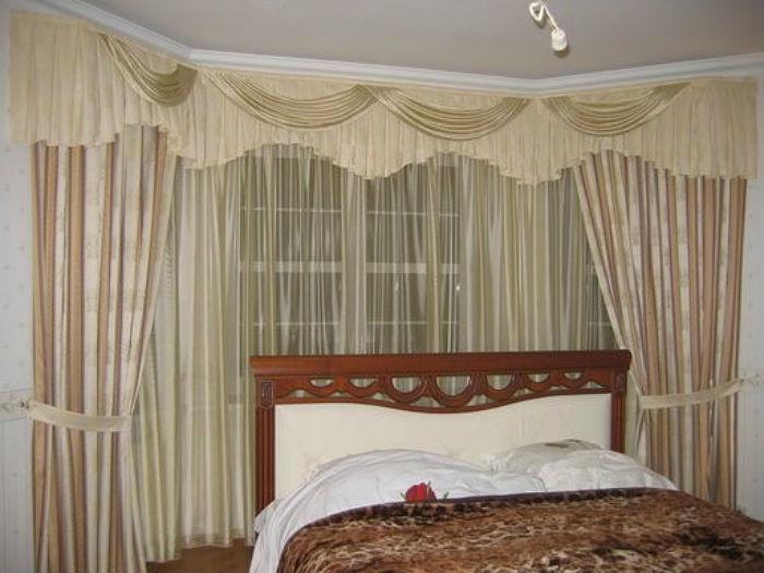 Небольшое пространство спальни лучше оформить угловыми шторами в пастельных тонах, так интерьер не будет казаться перегруженным и тяжелым